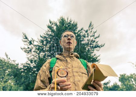 Image from bottom of surprised man with compass and notepad in autumn forest during day