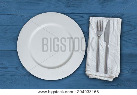 Empty plate with cutlery on blue vintage wood.