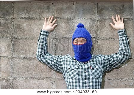 Masked thief raised arms with brick wall background. Catch burglar concept.