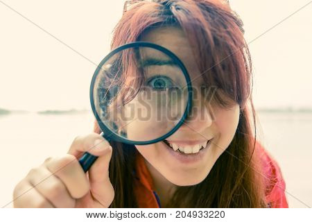 Portrait of woman with magnifier on blurred background during day