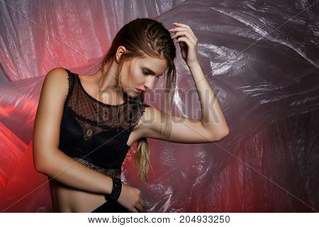 Eauty Portrait Of A Young Girl In Black Clothes. Gray-red Background, Flying Film