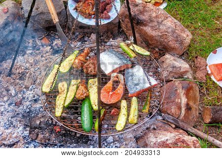 Garden grill on charcoal fire salmon zucchini chicken
