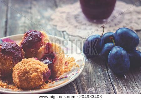 Plum dumplings, plums and plum sauce on wooden background