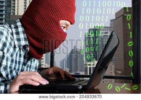 Masked hacker wearing a balaclava hacking data from laptop against digital city background