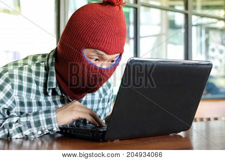 Masked hacker wearing a balaclava stealing data from laptop. Internet security concept.