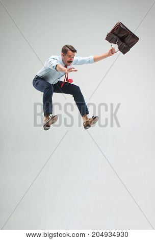 Businessman running or jumping with a briefcase, isolated on gray studio background