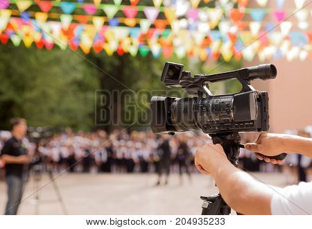 Camera man with video camera shoots cinema in sunny day