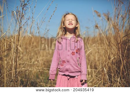 happy cute little girl smiling and she squints against the sun in the autumn on the nature walk outdoors