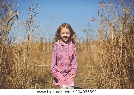 happy little girl smiling in the autumn on the nature walk outdoors