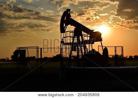 Horsehead oil pump in action during sunset time