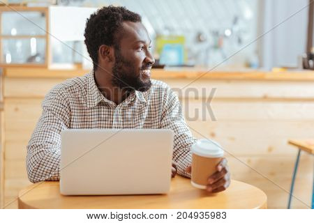In search of inspiration. Pleasant young man sitting in front of the laptop in a cafe, holding a cup of coffee and looking into the distance as if looking for inspiration