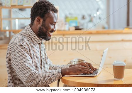 Diligent worker. Pleasant upbeat young man sitting at the table in the cafe and typing on the laptop keyboard while smiling broadly