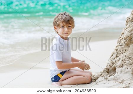 Happy funny little preschool kid boy having fun with building a sand castle on ocean beach. child playing on family vacations on tropical island. summer, happiness, childhood concept