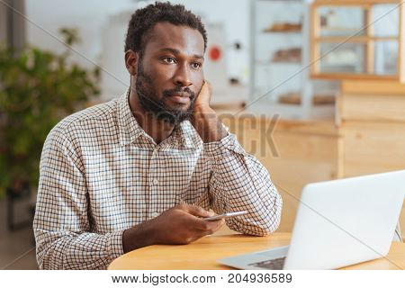 Pensive mood. Handsome young man sitting in the cafe, holding his phone and staring into the distance, thinking over a text message and being upset about it