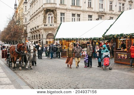 Prague, December 24, 2016: Old Town Square in Prague on Christmas Day. Christmas market in the main square. Celebrating Christmas. Happy local residents and tourists walk and rest. Europe. Holidays.