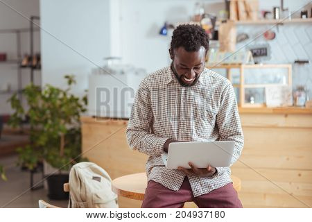 Beaming with happiness. Upbeat young man sitting on the table in the coffee shop and working on the laptop while smiling happily and broadly