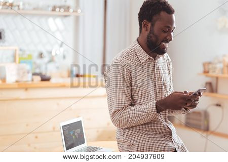 Pleasant chat. Cheerful young man sitting on the table in coffee shop and texting his friends on the phone while smiling pleasantly