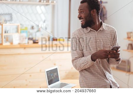 Happy man. Upbeat young man sitting on the table in the coffee house and turning to the sound of his name, looking at that person while texting with friends