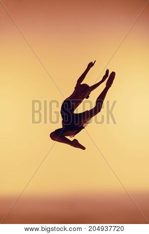 Beautiful young ballet dancer jumping on orange background.