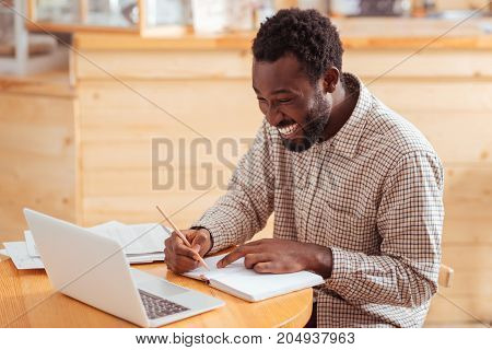 Thorough planning. Handsome joyful man sitting at the table in coffeehouse and planning his daily schedule in the notebook while smiling happily