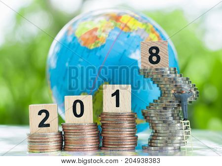 Businessman going up the stairs with a wooden numbers 2018 on growing stack of coins and globe background using as growing business ambition and achievement concept.