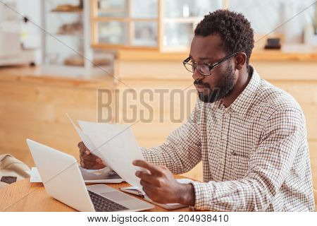 Attentive reading. Handsome young man in spectacles sitting in the coffeehouse and reading the documents in his hands