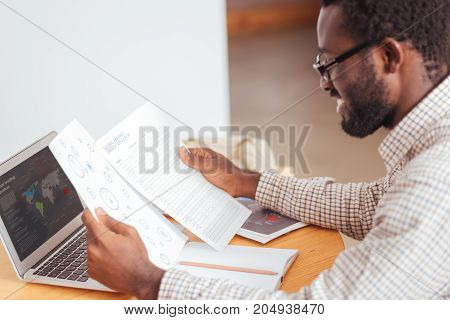 Thorough preparation. Handsome young man sitting at the table in the cafe and looking through the results of global market energy research, preparing his speech for presentation