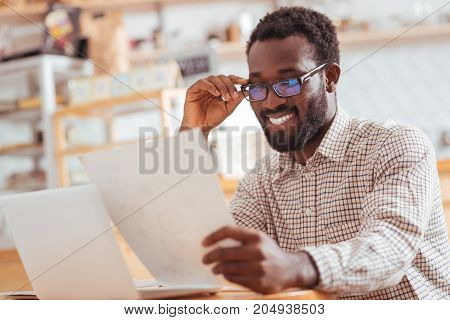 Content with results. Pleasant joyful young man sitting in the coffee shop and looking through the printouts with research results, looking content with them