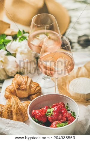 French style romantic summer picnic setting. Flat-lay of glasses of rose wine with ice, fresh strawberries, croissants, brie cheese, hat, sunglasses, peony flowers. Outdoor gathering concept