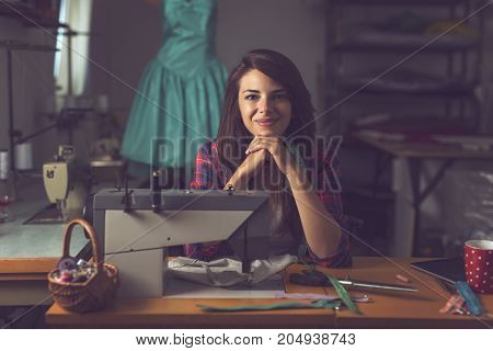 Young fashion designer sitting at a sewing machine in her workshop taking a break from work and thinking about new designs