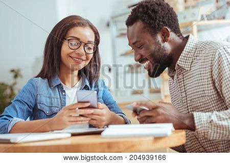 Hilarious content. Pretty young woman sitting at the coffeehouse with her male colleague and showing him funny posts on the phone while taking a break from work