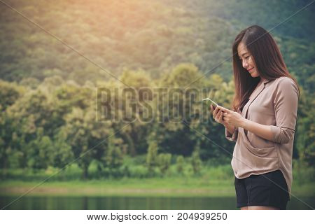 Closeup portrait image of a smiley beautiful Asian woman holding using and looking at smart phone at outdoor with mountain green nature and lake background