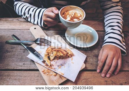 Top view image of a woman holding and drinking hot latte coffee with a piece of raisin danish on wooden vintage table in coffee shop