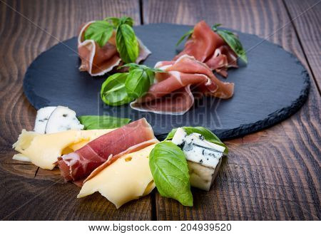 Prosciutto ham with basil leaves on black stone background