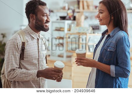 Quality time. Pleasant young man and woman talking to each other while holding paper cups with coffee, having bought them in the cafe