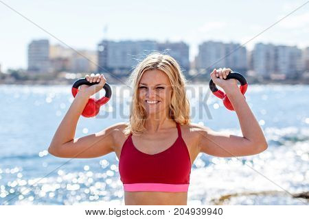 Young blonde woman in sportswear holding kettlebells outdoor at seashore