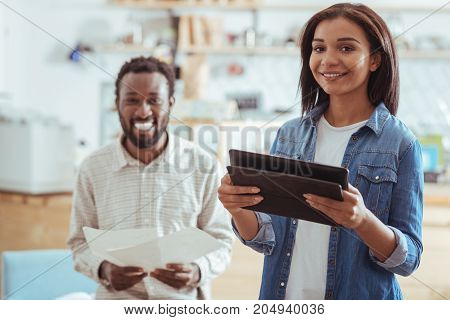 Diligent preparation. Pleasant young woman and her male colleague preparing to give presentation about their startup while the woman revising speech from tablet and the man from printouts
