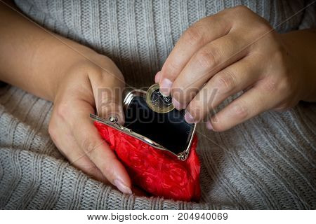 A woman puts a coin in an empty purse. Red coin purse.