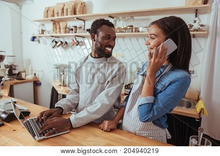 Pleasant working day. Two pleasant baristas in aprons standing behind the cafe counter, the man updating the menu on the website while the woman talking on the phone