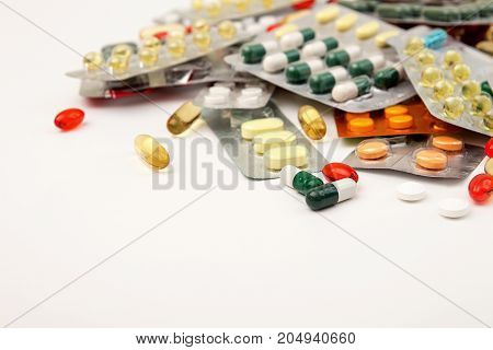 Heap Of Medicine Tablets And Pills In Blisters Different Colors On White Background. Healthcare Or M