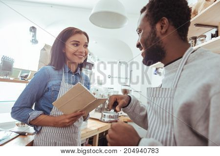 Clear explanation. Pleasant experienced male barista showing his new female colleague a portafilter and expressing her how to use it while the woman making notes