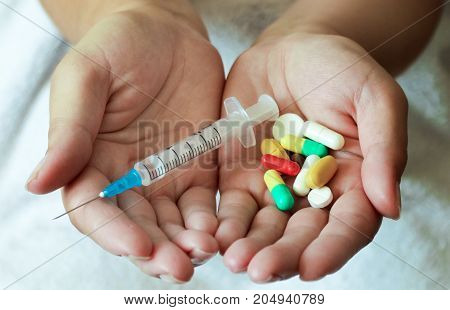 Young woman holding a syringe and pills. Disease fever pain.