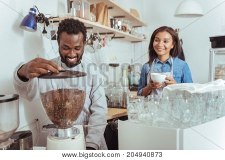 Modern equipment. Charming young male barista using a coffee machine to make some coffee for himself while his female colleague holding a cup of coffee already