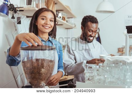 Practice makes perfect. Beautiful young woman using a coffee machine and making coffee while her smiling male colleague tasting it