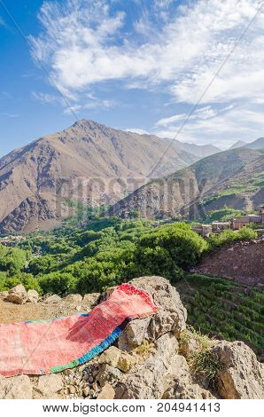 View on beautiful High Atlas Mountains landscape with lush green valley and rocky peaks, Morocco, North Africa.