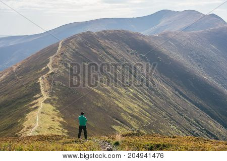 Hiking man, climber or trail runner in mountains, inspirational landscape. Motivated hiker with backpack looking at mountain view. Trekking, travel and tourism concept. Fitness and healthy lifestyle.