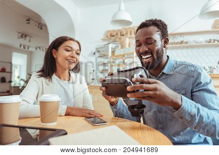 State-of-the-art technology. Pleasant young friends sitting at the table in the cafe and scrutinizing a new VR headset in the hands of the smiling man