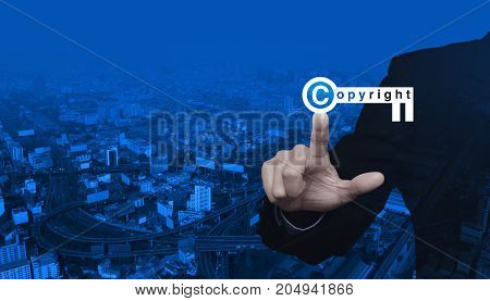Businessman pressing copyright key icon over modern city tower street and expressway Copyright and patents concept
