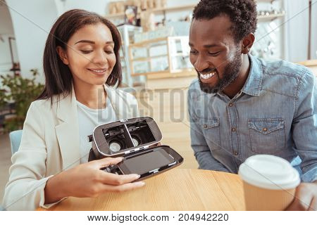 Ready for use. Upbeat young man sitting in the cafe together with his best friend and watching her insert her smartphone into a VR headset