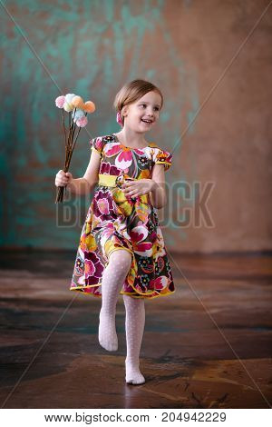 Happy smiling and dancing Cute little girl on the interior studio